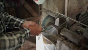 Worker grinding a metal part with grinding wheel. At home stock video footage