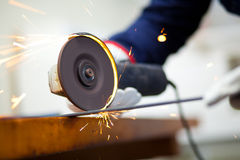 Worker grinding a metal plate. Close up Stock Images