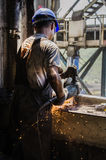 Worker grinding a metal plate. Royalty Free Stock Images