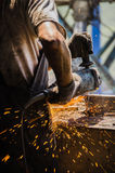 Worker grinding a metal plate. Royalty Free Stock Image