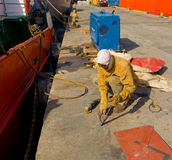 A worker grinding metal at a shipyard in the tropics Stock Photography
