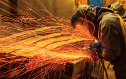 Worker grinding parts with sparks Royalty Free Stock Image