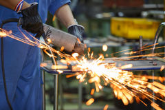 Worker grinding steel by electric grinding machine Royalty Free Stock Photography