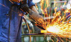Worker grinding steel by electric grinding machine Stock Images