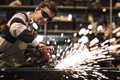 Worker grinding steel. Grinding steel pieces using grinder royalty free stock photos