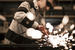 Worker grinding. Grinding steel pieces using grinder royalty free stock images