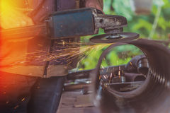 Worker grinding steel pipe with grinder Royalty Free Stock Photography