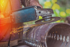Worker grinding steel pipe with grinder Stock Photos