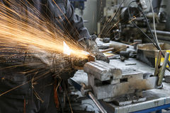 Worker grinding steel table Stock Images