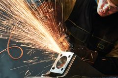 Worker grinding weld seam with grinder machine and sparks. Industrial worker grinding and sanding weld joint with grinder machine with spark Royalty Free Stock Image