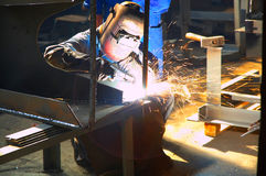 Worker grinding/welding metal. Worker with protective mask and gloves grinding/welding metal and sparks spreading, in a factory Royalty Free Stock Images