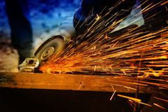 Worker grinding/welding metal and sparks spreadi stock images