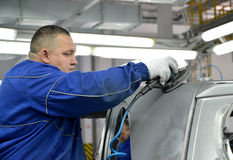 The worker grinds a car body. Automobile plant Stock Photos