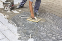 Worker grouting tiles. With rubber trowel and gray cement mortar Royalty Free Stock Images