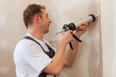 Worker grouts with silicone Royalty Free Stock Photos