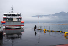 Worker guides ferry to Miyajima ferry pier in Miyajima Stock Photo
