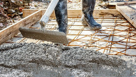 Worker with gum boots spreading ready mix concrete Stock Photo
