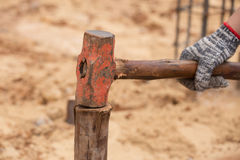 Worker hammering eucalyptus pointed Stock Photo