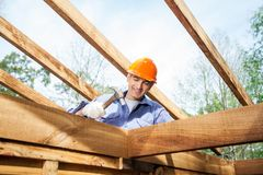 Worker Hammering Nail On Incomplete Timber Cabin Stock Images