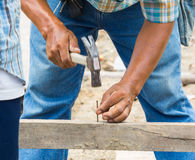Worker hammering nail into wood Stock Photos