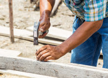 Worker hammering nail into wood Stock Photo