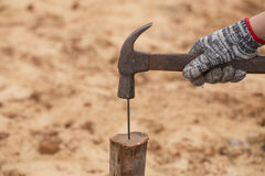 Worker hammering nail into wood Royalty Free Stock Photos
