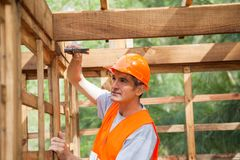 Worker Hammering Nail On Wooden Cabin Stock Image