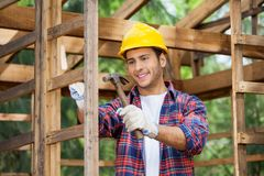 Worker Hammering Nail On Wooden Cabin Stock Photo