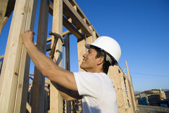 Worker Hammering Nail On Wooden Wall Stock Image