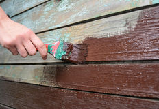 Worker hand with brush painting and repair wooden wall. How to Paint Old Wooden Surface. Stock Photos