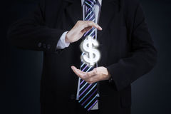 Worker hand with dollar symbol. Picture of a male worker hands holding a dollar currency symbol and wearing formal suit royalty free stock photo