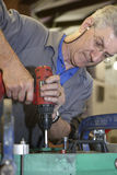 Worker and hand drill Royalty Free Stock Photography