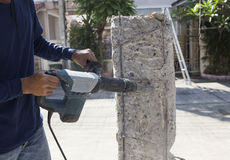 Worker hand drilling on concrete pole for construction building Stock Photography