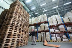 Worker with hand pallet truck at large  stack of wooden pallets in storehouse. Wide angle lens Stock Photo