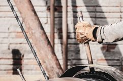 Worker hand pulling the lever of a pile driver. Bate-estaca. Construction worker. Hand holding a lever. Worker hand wearing worn out gloves triggering a motor stock photography