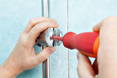 Worker hand with screwdriver adjust angle adjustable bracket hol. Repair of bathroom, closeup plumbers hand tighten the screw adjustable shower handle bracket Royalty Free Stock Photos