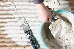 Worker hand with spatula and plaster, build work. Unrecognizable worker with white plaster, dirty hand with spatula. Construction renovation background with free Royalty Free Stock Photography