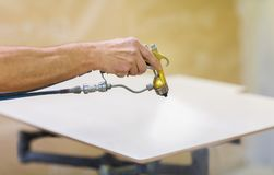 Worker hand sprays urethane finish to board. Production, manufacture and woodworking industry concept - worker hand sprays urethane finish or polish to board at stock image