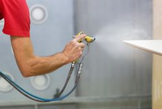 Worker hand sprays urethane finish to board Stock Photo