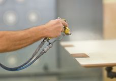 Worker hand sprays urethane finish to board. Production, manufacture and woodworking industry concept - worker hand sprays urethane finish or polish to board at stock photo