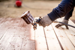 Worker hand using spray gun and painting wood Royalty Free Stock Photos