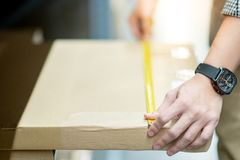 Worker hand using tape measure on cardboard box. Male worker hand using tape measure for measuring dimension of product in cardboard box. Shopping lifestyle in Stock Photos