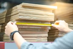 Worker hand using tape measure on cardboard box. Male worker hand using tape measure for measuring dimension of product in cardboard box. Shopping lifestyle in Royalty Free Stock Photography