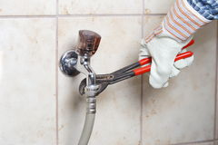 Worker hand. Workman is fixing a water pipe with gripper and glove Royalty Free Stock Image