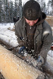 Worker handles a log using planing machine. Stock Photo