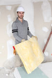Worker handling square of insulation. Worker handling new insulation material royalty free stock photography