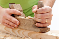 Worker hands closeup - planing wood Royalty Free Stock Image