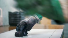 Worker hands in gloves lubricates the printed edition. Close up stock video footage