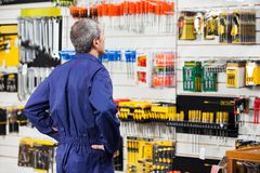 Worker With Hands On Hip In Hardware Store. Rear view of worker with hands on hip standing in hardware store Royalty Free Stock Image