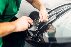 Worker hands installs car paint protection film Royalty Free Stock Images